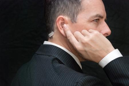 agente: Close-up di un agente dei servizi segreti ascoltando il suo auricolare, lato.