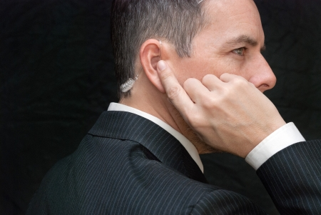 Close-up of a secret service agent listening to his earpiece, side.