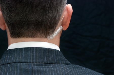 secret agent: Close-up of a secret service agent, behind. Stock Photo