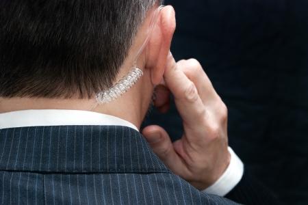背後にある彼のイヤホンを聞いてシークレット サービス エージェントのクローズ アップ。 写真素材