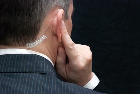 earpiece: Close-up of a secret service agent listening to his earpiece, over the shoulder. Stock Photo