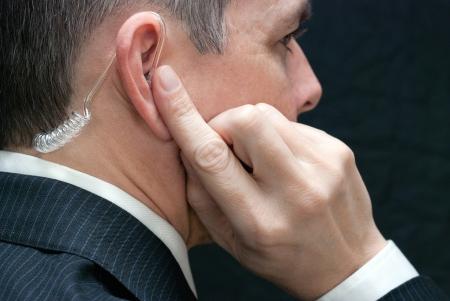 secret service: Close-up of a secret service agent listening to his earpiece, close side.