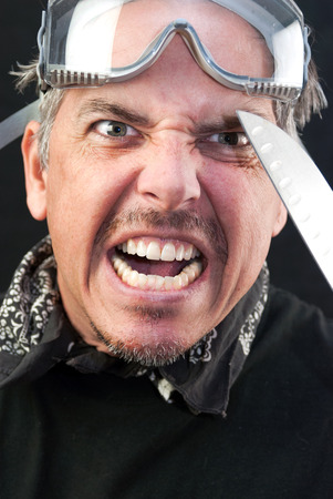 Close-up of a crazy man attacking with a knife. photo