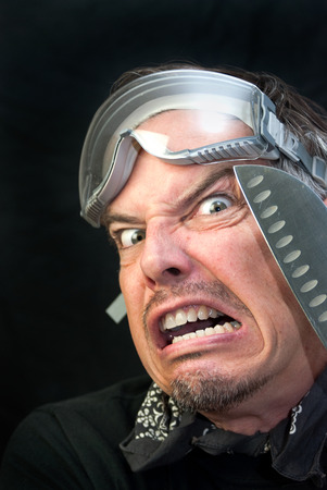 Close-up of a crazy man wearing goggles with a knife loking afraid. photo