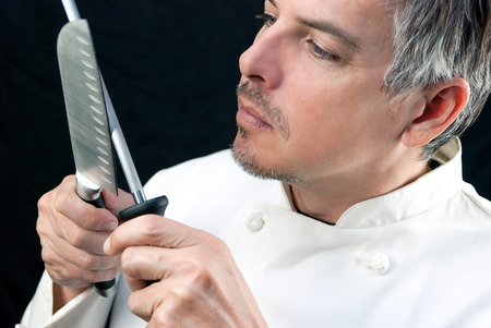 sharpener: Close-up of a chef sharpening his knife.