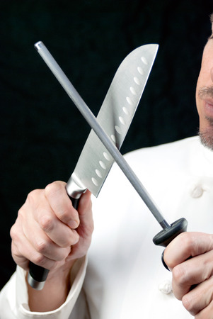 sharpening: Close-up of a chef sharpening his knife, side.