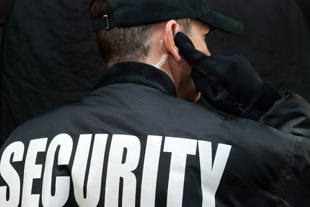 彼のイヤホンを聞いてセキュリティ ガードのクローズ アップ