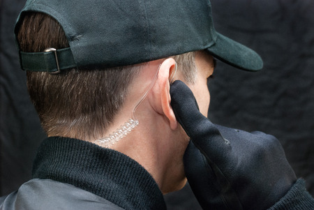 Close-up of a security guard listening to his earpiece 版權商用圖片