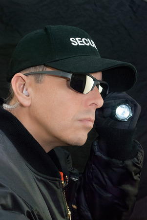 earpiece: Close-up of a security guard searching with his flashlight.