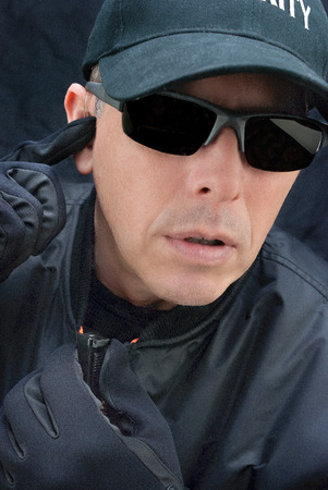 earpiece: Close-up of a close protection officer reporting  Stock Photo