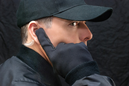 earpiece: Close-up of a close protection guard scanning for threats