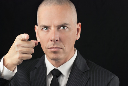 Close-up of an intense bald man pointing to camera