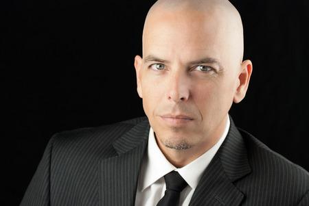 Close-up of an intense bald man looking to camera