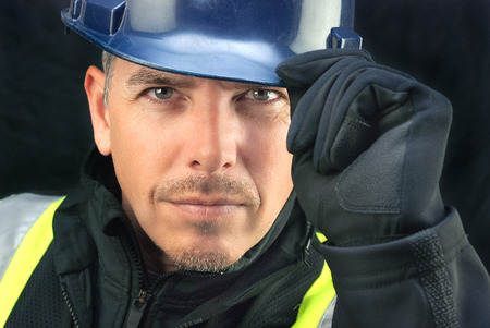 Close-up of a construction worker putting on his hardhat  photo