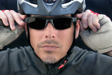 Close-up of bicycle courier putting on his sunglasses  Standard-Bild