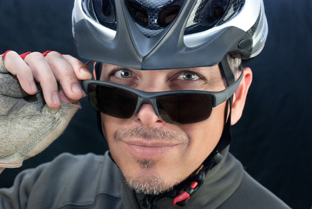 Close-up of friendly bicycle courierlooks over his sunglasses