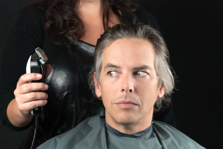 hair stylist: Close-up of a hair stylist preparing to use clipper having removed bulk length. Stock Photo