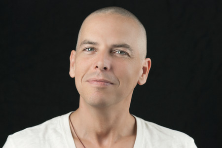 shaved head: Close-up of a man with a newly shaved head looking to camera. Stock Photo