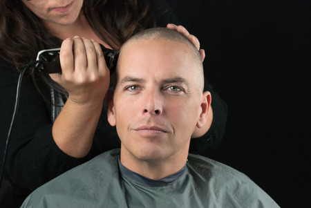 hair stylist: Close-up of a hair stylist using clippers to shave her Clients head. Stock Photo