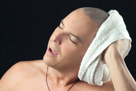 shaved: Close-up of a man towel drying his newly shaved head. Stock Photo