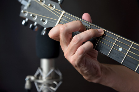 fingering: Close-up of the fingering for a C7 sustained chord on a left handed classical guitar. Stock Photo