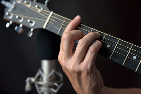 fingering: Close-up of the fingering for an F sharp chord on a left handed classical guitar.
