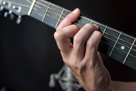 fingering: Close-up of the fingering for a G major chord on a left handed classical guitar.