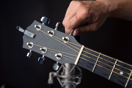 fingering: Close-up of a hand turning a guitars tuning pegs with a studio microphone in the background.