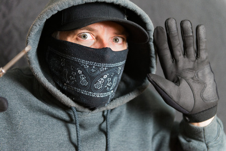 swindler: Close-up of a burglar busted, with his hands and tools up Stock Photo