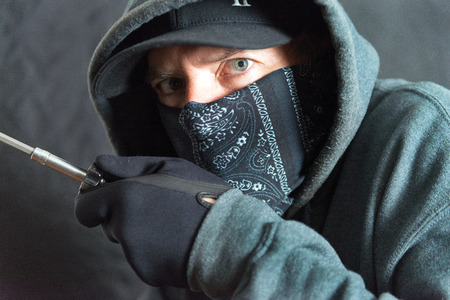 Close-up of a burglar breaking in, right side of frame