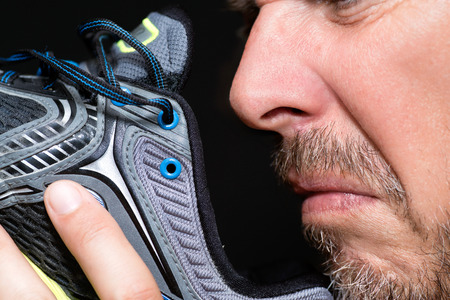 smelly: Close-up of a man smelling his running shoe. Stock Photo