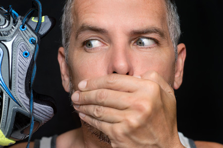 Close-up of a man covering his mouth after smelling his running shoe.