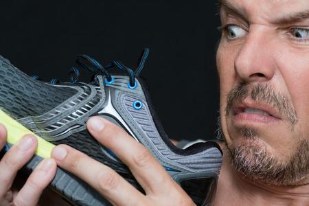 Primer plano de un hombre disgustado por el olor de su zapatilla deportiva.