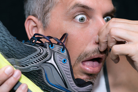 stink: Close-up of a man gagging after smelling his running shoe. Stock Photo