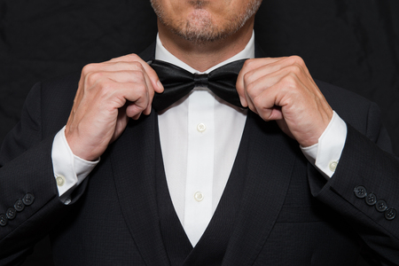 coat and tie: Close-up of a gentleman wearing Black Tie straightens his bowtie.