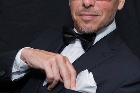 Close-up of a gentleman wearing Black Tie fixes his pocket square, horizontal.
