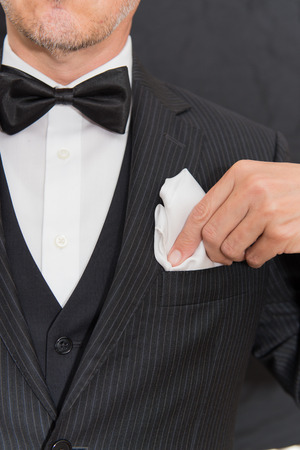 formal attire: Close-up of a gentleman wearing Black Tie fixes his pocket square, vertical. Stock Photo
