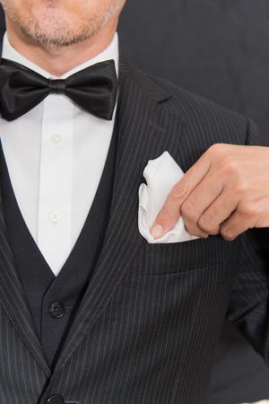 hombres maduros: Primer plano de un caballero que lleva Negro Tie fija su pa�uelo de bolsillo, vertical.