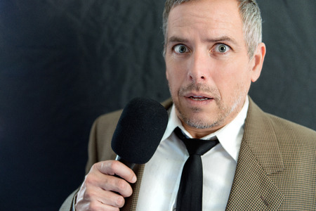 public speaking: Close-up of an anxious man speaking into microphone. Stock Photo