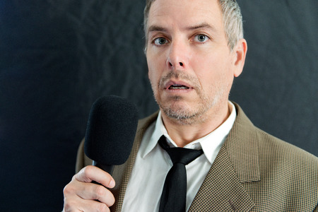 speaking: Close-up of a depressed man speaking into microphone. Stock Photo