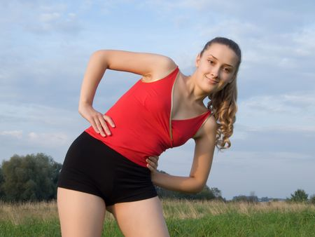 Sporty girl in red exercising on meadow against the sky.