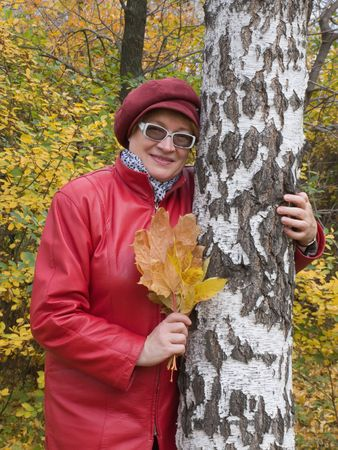 Smiling old lady in red stays in autumn park. Stock Photo - 3696367