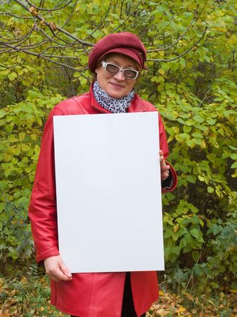 Smiling old lady in red holds an empty poster. Stock Photo - 3696364