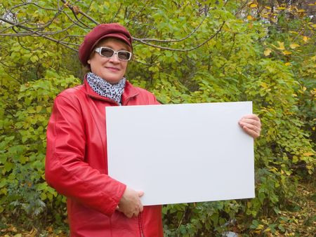 Smiling old lady in red holds an empty poster. Stock Photo - 3747532