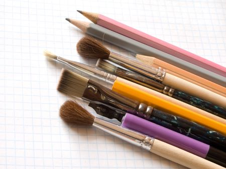 pencils and brushes  on squared sheet of a copybook Stock Photo - 3768312