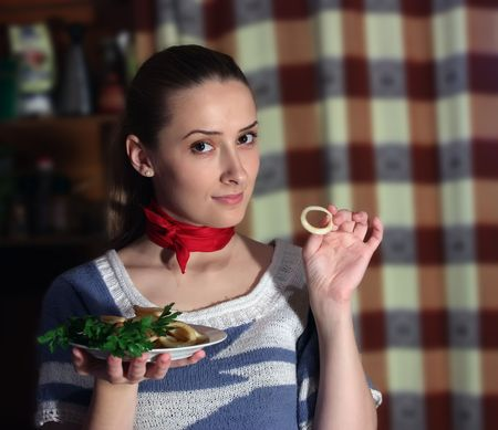 ingridients: Young woman eating fried calamar in kitchen