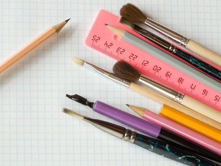pencils and brushes on squared sheet of a copybook Stock Photo - 3825542
