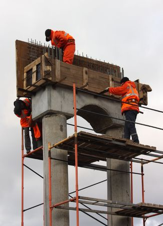 Top men in orange working on concrete piles