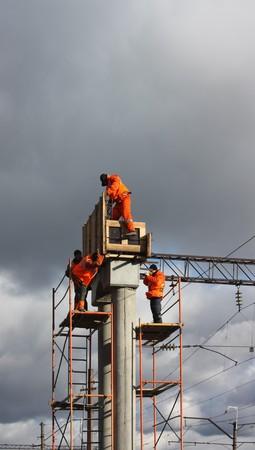 subcontractors: builder in orange working on concrete piles  Stock Photo
