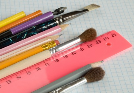 pencils and brushes on squared sheet of a copybook Stock Photo - 4167703